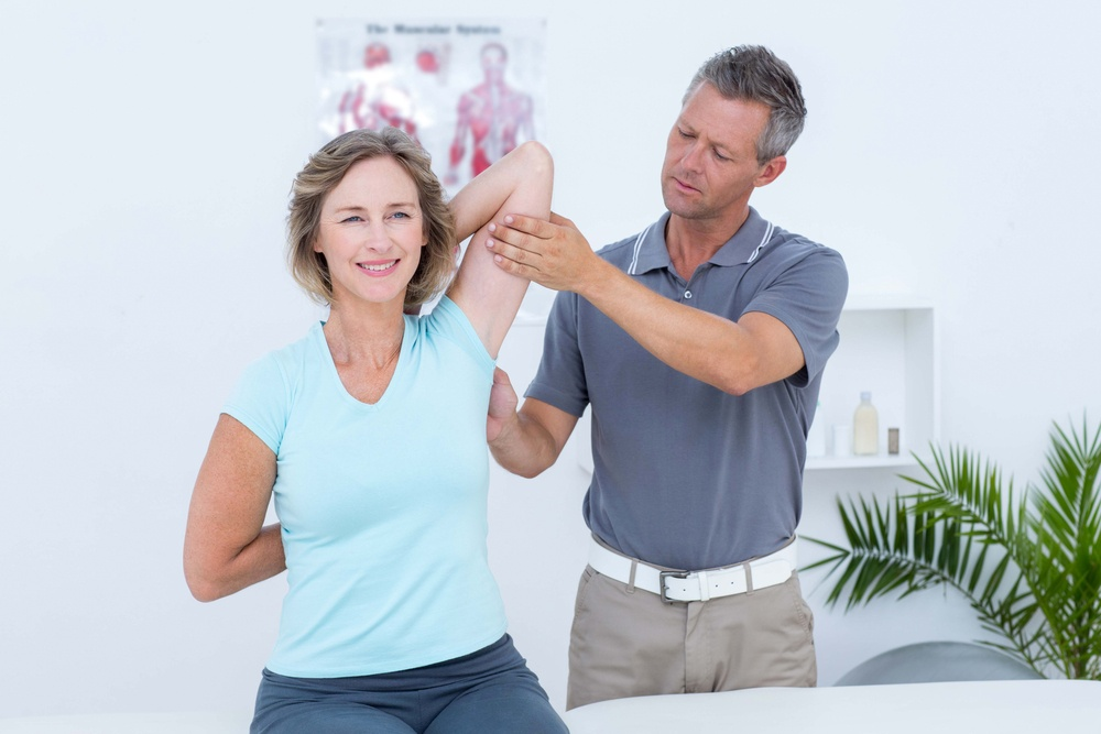 Woman stretching her arms with her doctor in medical office